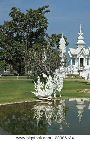 Fantastic snow-white palace. It is built in style of new Thai architecture. It is superb reflected in a pond with alive small fishes