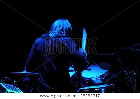 Drummer is playing. The light setting is blue. Note the stick is in motion blur.