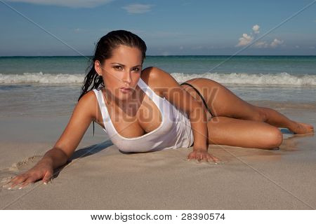 Seductive model lying looking at the camera on a sandy beach and showing her cleavage, ocean and surf behind