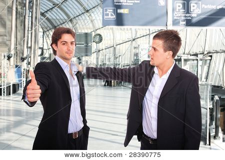 Two handsome young businessmen at the train station