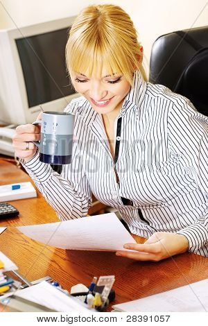 Blond Businesswoman Checking The Papers In Office