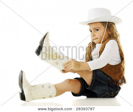 An adorable young cowgirl putting on her boots.  On a white background.