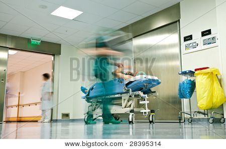 Blurred figures of people with medical uniforms transporting a patient to surgery