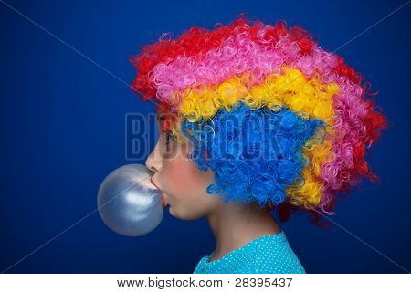 Young girl blowing chewing gum balloon over blue background