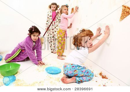 Group of elementary children cleaning up after food fight at slumber party with pizza and popcorn.