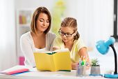education, family and learning concept - mother and daughter doing homework together and reading boo poster