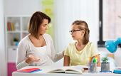 education, family and learning concept - displeased mother talking to daughter while doing homework  poster