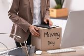 Young Woman Holding Moving Box With Office Stuff Indoors, Closeup poster