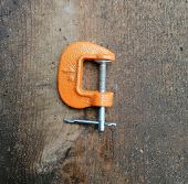 Metal Orange Clamp, Small, New On Wooden Background poster