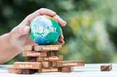 Save World Or Earth Day Concept. Hands Holding Model Globe Clay On Wooden Block Tower For Letter E.g poster