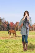 foto of hay fever  - A beautiful woman with a cold hay fever or allergies blowing her nose - JPG