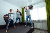 Happy Family, Dad, Mom And Son Spend Time Together, Fooling Around On The Bed, Beating With Pillows. poster