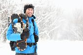 Winter snowshoeing. Young outdoorsman hiker standing smiling happy holding snowshoes outside in the