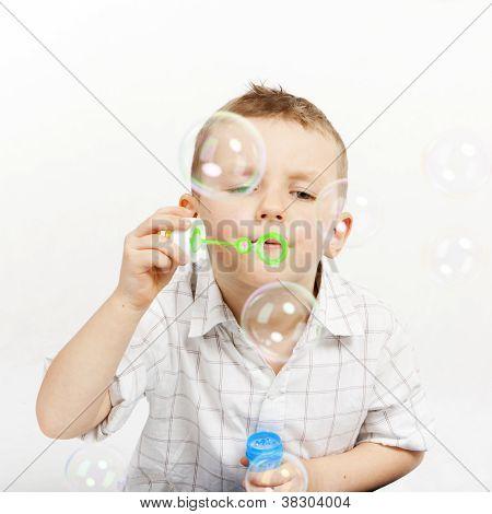 Pretty, cute boy blowing soap bubbles