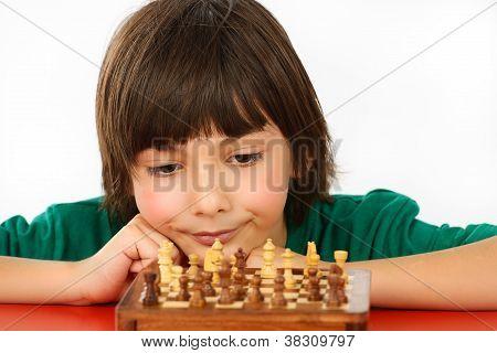 Niño pensando en una partida de ajedrez, aislada sobre fondo blanco