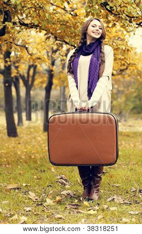 Beautiful Girl With Suitcase At Autumn Park.