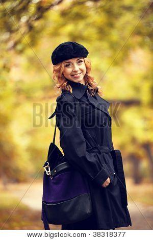 Redhead girl in the autumn park.