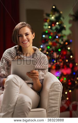 Happy Woman In Front Of Christmas Tree Holding Tablet Pc