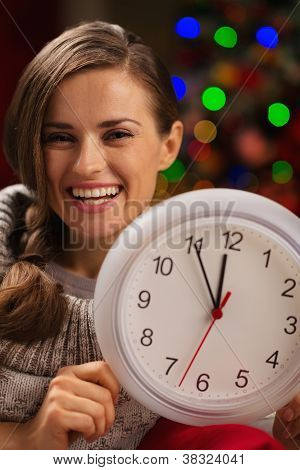 Portrait Of Smiling Woman Showing Clock In Front Of Christmas Li