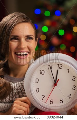 Portrait Of Happy Woman Showing Clock In Front Of Christmas Ligh