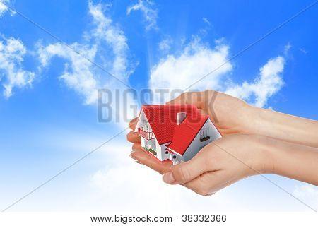 a casa em mãos no céu azul