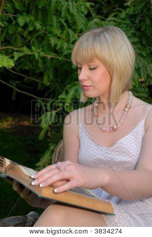 Cute Blond Reads Book In Garden