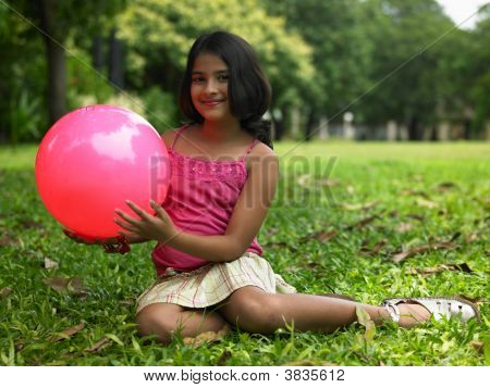 Asian Girl In The Garden With Her Ball