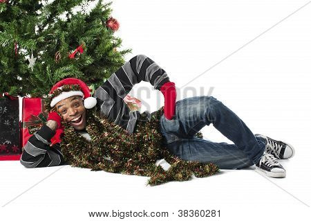 Happy African American Man Lying Beside A Christmas Tree