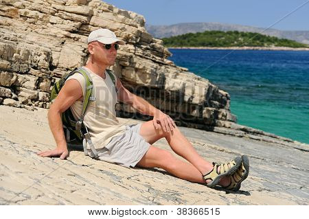 Outdoor man resting on rock after hiking Croatia