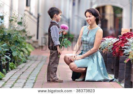 Little Son Giving A Flower To Mother
