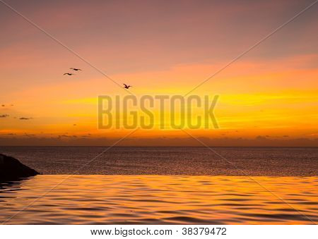 Infinity Edge Pool With Sea Underneath Sunset