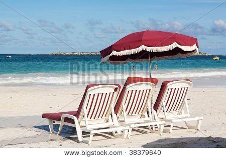 Three Beach Loungers And Umbrella On Sand