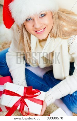 woman wearing santa hat sitting on the floor