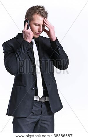 Business Man In A Black Suit And A Mobile Phone With Headache Isolated On White
