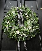 image of christmas wreath  - Eucalyptus Christmas wreath hung on a black door - JPG