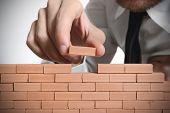 stock photo of brick block  - Concept of a man that build new business - JPG