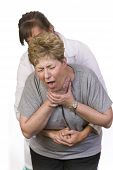 stock photo of choke  - Using the Heimlich Maneuver on a choking person