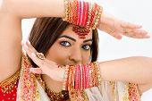stock photo of indian wedding  - Beautiful face of a Bengali bride with arms across her head covered with colorful bracelets isolated - JPG