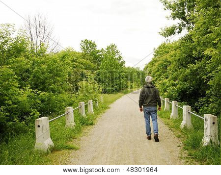 Man Walking a Dirt Road