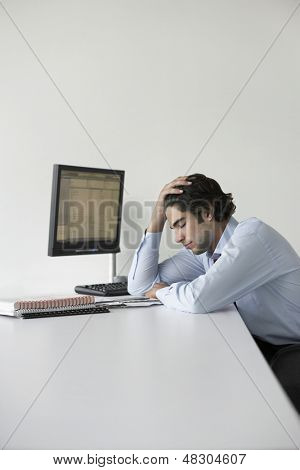 Side view of a young businessman with head in hands by computer sitting at office desk