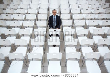 Portrait of confident businessman sitting on one of chairs