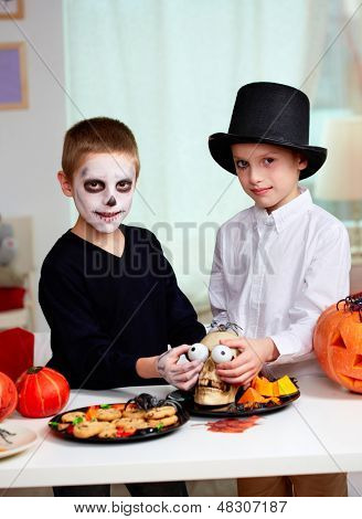 Photo of twin boys holding spooky eyes just in skull eye-sockets and looking at camera