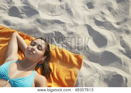 Elevated view of relaxed teenage girl listening music through earphones lying on beach towel
