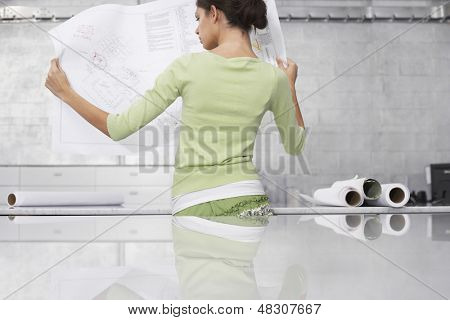 Rear view of young businesswoman reading blueprint at office