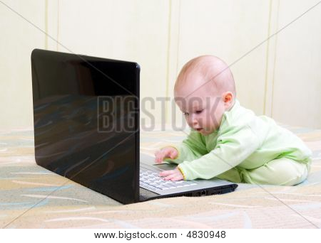 Little Girl With Lies On The Floor With A Laptop