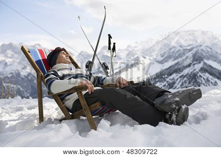 Side view of a man in warm clothing resting on deckchair in snowy mountains