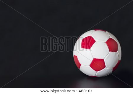 Red And White Soccer Ball On A Black Background
