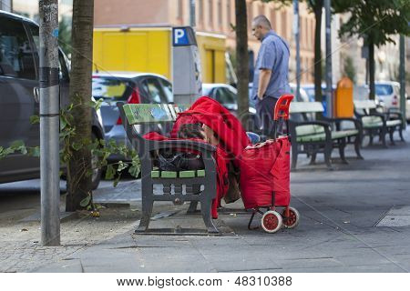 Homeless sleeping on a bench in the street