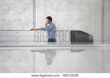 Young businessman using landline phone in office