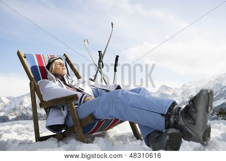 Side view of a woman resting on deckchair in snowy mountains